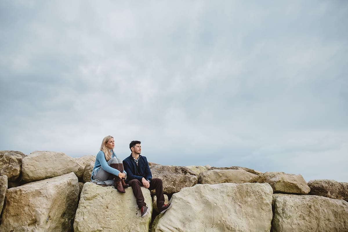dorset engagement photography - sitting on the rocks at highcliffe beach